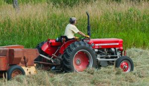 Farmer wearing noise-cancelling headphones while baling hay