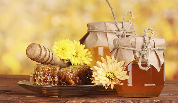 two jars of honey,honeycombs and drizzler on yellow background