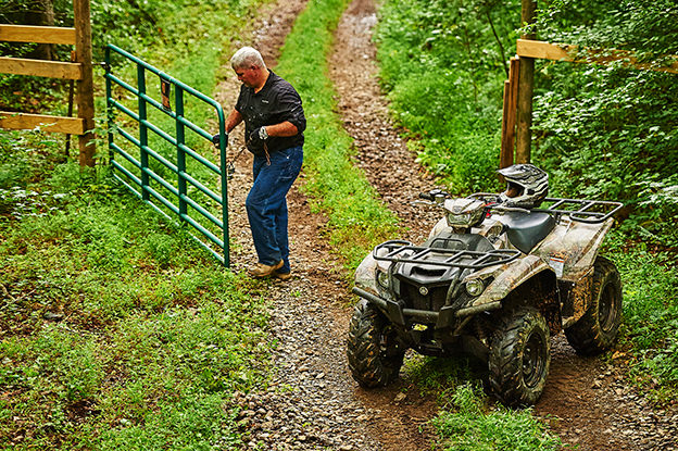 man on ATV moving gate